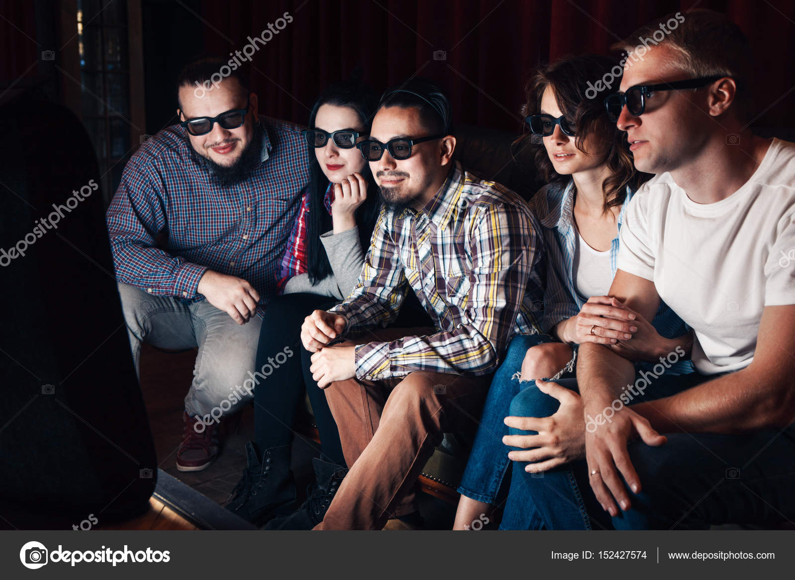 47a5d17dac38 Group of youth watching new movie in 3d glasses at home. Five young friends  have fun sitting on couch in front of tv for entertainment.