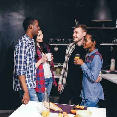 Company in kitchen, happy couples, communication