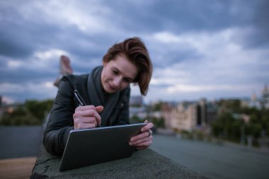 Designer with tablet drawing on roof
