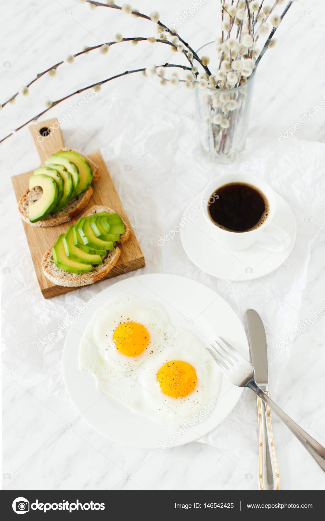 Morning breakfast table setting. On a white plate are two fried eggs on a wooden board sliced avocado a cup of coffee and a vase with a plant. & Morning breakfast table setting. u2014 Stock Photo © oksanastepova ...