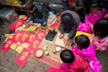 Hanoi, Vietnam - Jun 22, 2017: Old Dong Ho village artist making Dong Ho folk woodcut painting with children surrounded in communal house, Quoc Oai district. Concept of cultural preservation