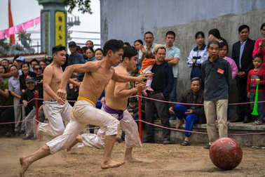 Hanoi, Vietnam - Feb 2, 2017: : Vietnamese men playing outdoor game at the traditional ball scrambling festival in Thuy Linh village, Linh Nam ward, Hoang Mai district, Hanoi