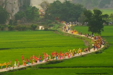 Ninh Binh, Vietnam - Apr 10, 2017: Thai Vi traditional spring festival with crowded people and palanquin, dancing dragon, flag...walking on curved soil road among rice field