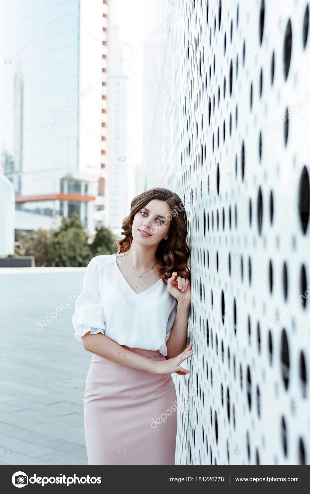 8f132f55421d Γραφείο στυλ. Ένα πορτρέτο επαγγελματίες της η νεαρή γυναίκα σε μια λευκή  μπλούζα και φούστα ροζ φόντο την πόλη αρχιτεκτονική — Εικόνα από balchugova