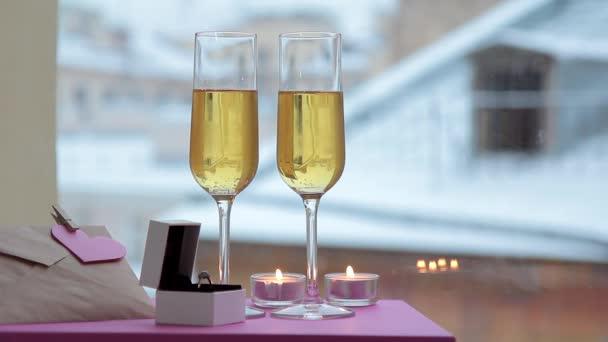 Auf dem Tisch stehen Gläser, ein Ring, brennende Kerzen für den Urlaub.