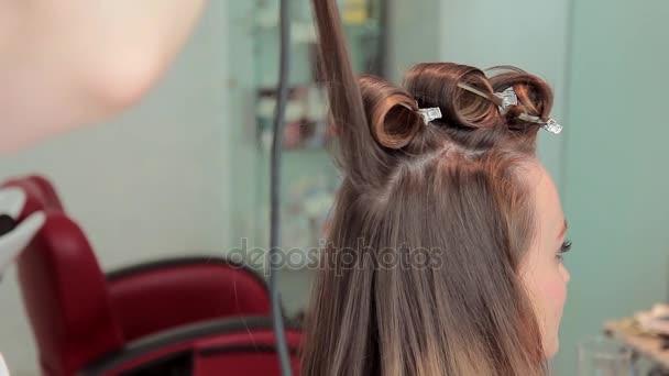 Kadeřník kroutí vlasy sedící ženy s kulmou