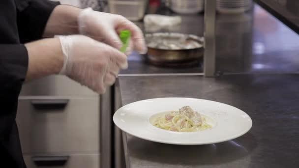 Náčelník dokončit výzdobu připravené jídlo z těstovin v kuchyni v restauraci či kavárně