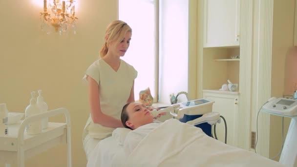 Mladí kosmetička provede masáž obličeje lpg pro ženu ležící v klinice