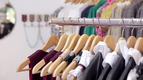Různé šaty na ramínka na kovových regálů v obchodě.