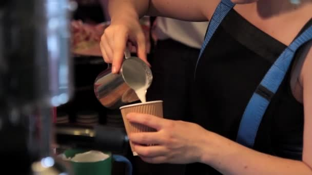 Woman pours milk into coffee in plastic cups indoor.