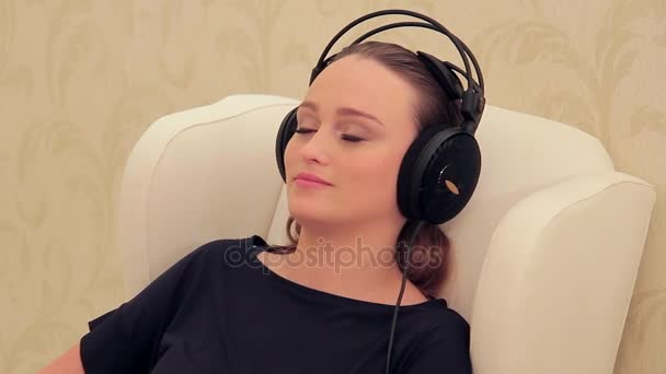 Young woman listening to music sitting indoors.