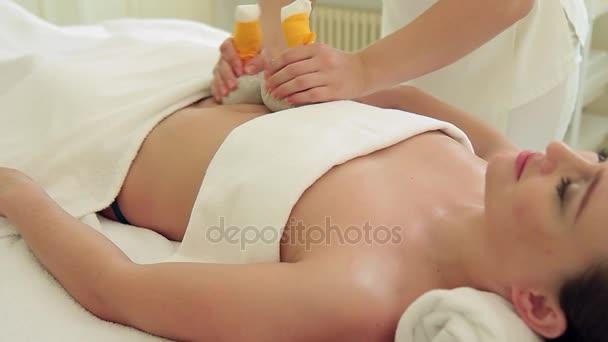 Thajské masáže s bylinné váčky pro mladou ženu ve spa salonu