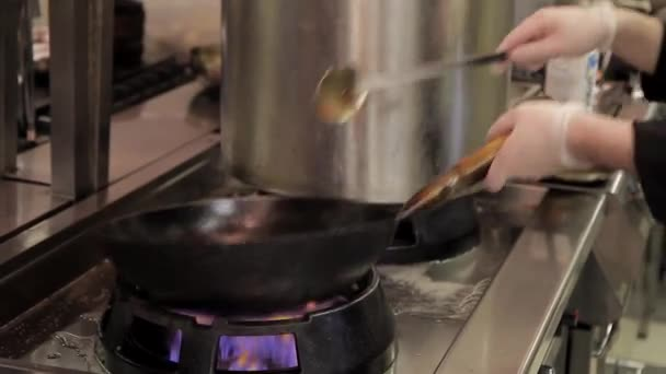 Chef fry different products wok on open fire in kitchen restaurant or cafe.