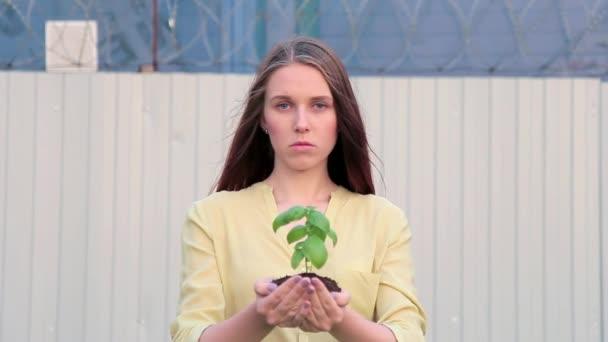 Zahradníka žena natahuje ruce s zelených rostlin stojící venku