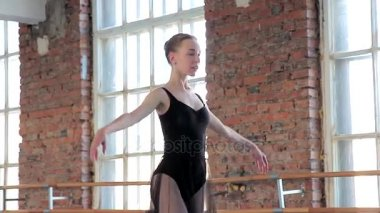 Ballerina using Arabesque position working leg lifted back knee pulled