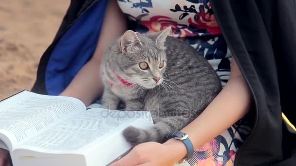 woman sitting on river bank, reading book, holding cat outdoors