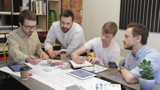 Coworkers discuss design sitting at the table in office.