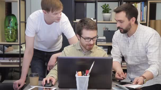 Uomini di colleghe spiega i piani di lavoro seduto dietro il computer portatile allinterno di office
