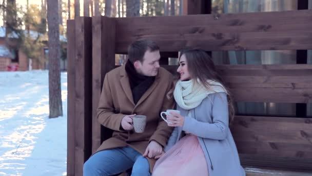 Mladý muž a žena, líbání, sedí na lavičce drží hrnky venkovní.