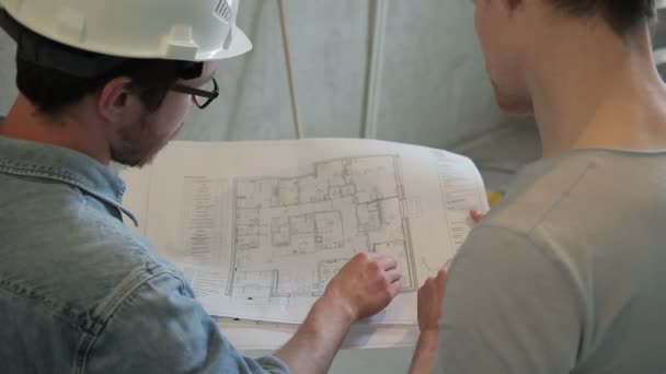 Two architects analyze blueprint of building standing indoors two architects analyze blueprint of building standing indoors stock video malvernweather Gallery