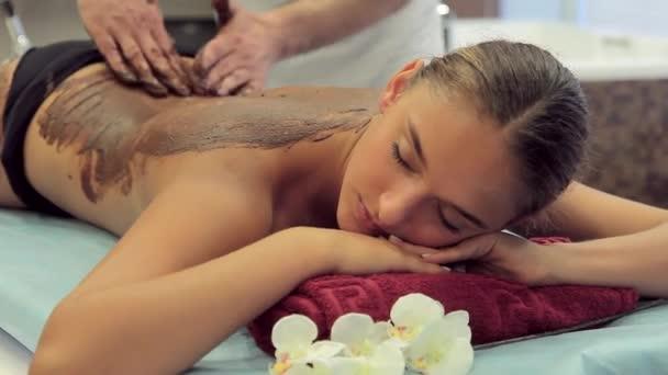 Kosmetička použije čokoládový peeling na zadní ležící žena ve spa salonu.