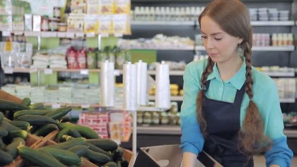 Prodávající rozvrhnout zeleninu boxy pro prodej v supermarketu