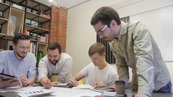 Lustige Typen mit Bart malen eine Zeichnung auf dem Schreibtisch.
