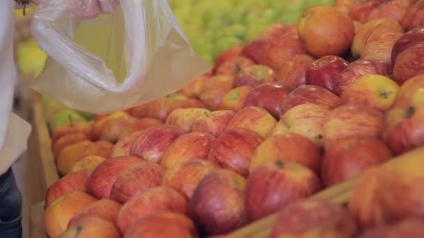 Žena dává pečená jablka v plastovém sáčku v supermarketu uvnitř