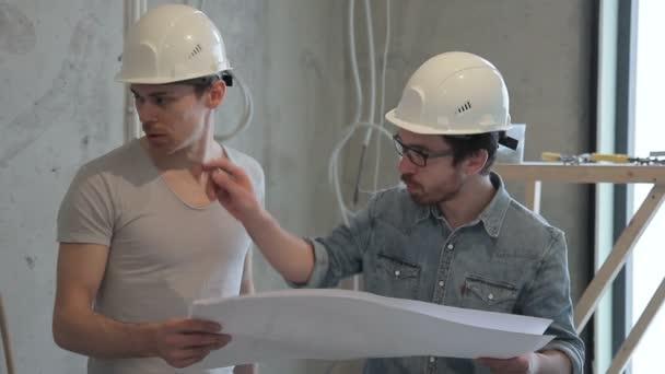 Mistr vysvětluje fungování plánu oprav v pokoji na papíře