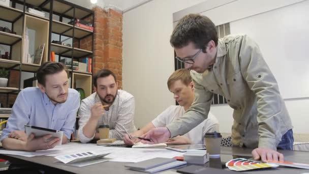 Arbeitnehmer, die über Geschäfte mit Tablets diskutieren, sitzen im Büro am Tisch.