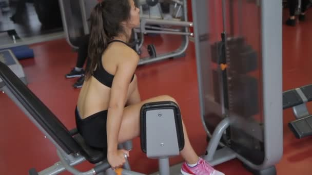 Young woman athlete doing exercise for legs in gym indoors.