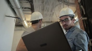 Two architects in helmets talking looking at laptop standing at construction site. Specialist holds laptop.