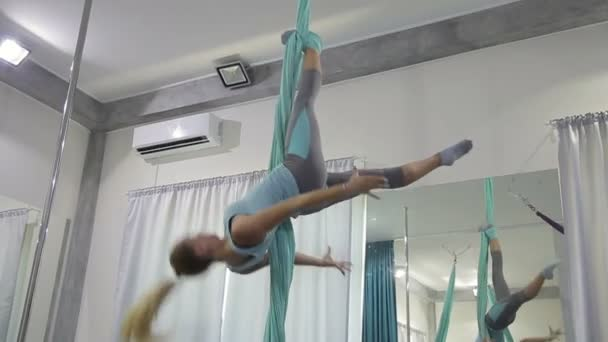 Flexible blonde woman descends down on air canvases.
