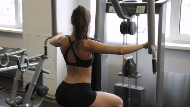 Female athlete doing reverse Pec-Deck flye in gym indoors.