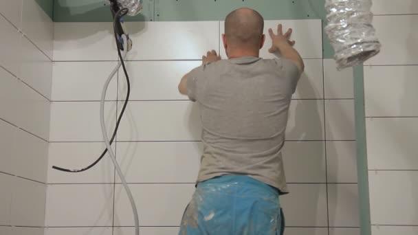 Muž ruce pevně připojí dlaždice na stěně nahoře