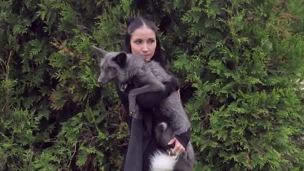 Atraktivní bruneta s gray fox pózuje před kamerou v parku venku