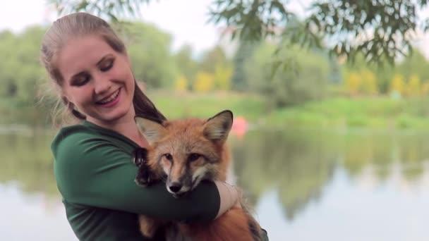Pěkná žena drží v rukou, fotografoval s divoké zvíře venku fox
