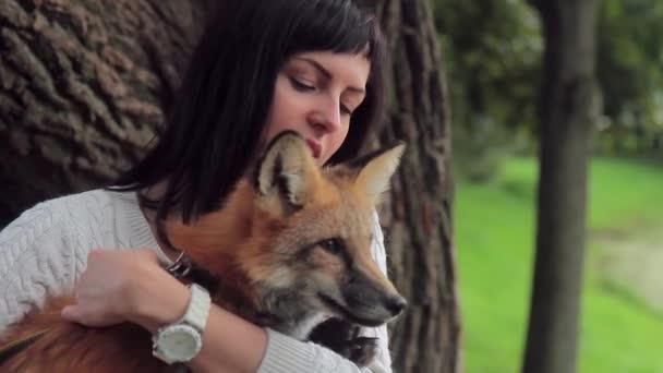 Krásná žena s náramkových hodinek má liška poblíž stromu
