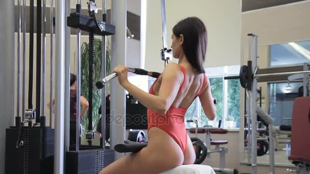 Sexy female athlete swings muscles while sitting on training machine.