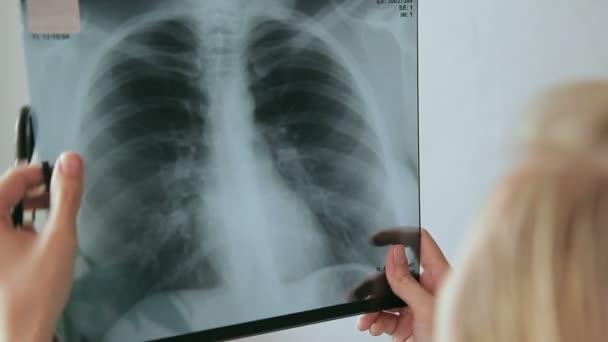 Female doctor examines blonde picture rengenta chest.