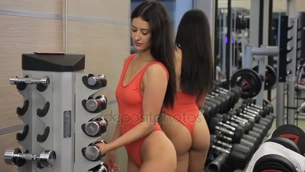 Sexy žena v těsných plavkách se činka z čítače s tělocvičnou.