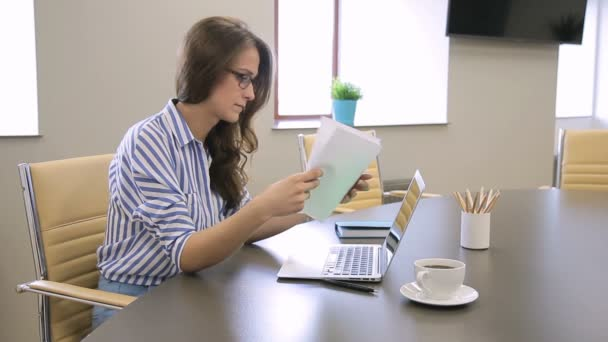 In office woman looks at documents with charts and prints on laptop.