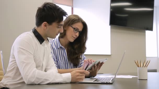 Man and woman working with laptop and tablet while sitting in office.