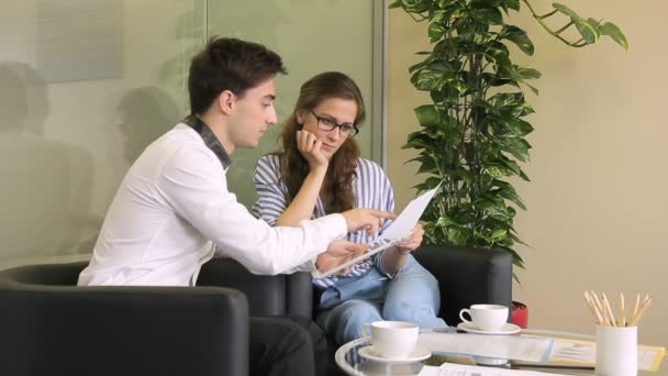 Young employees talk over cup of coffee in large company.