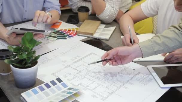 Tým návrhářů práce u stolu v kanceláři pomocí tabletu.