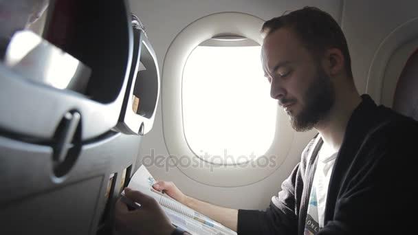 Ein unrasierter Mann liest in einem Flugzeug in der Nähe von Bullaugen eine Zeitschrift.