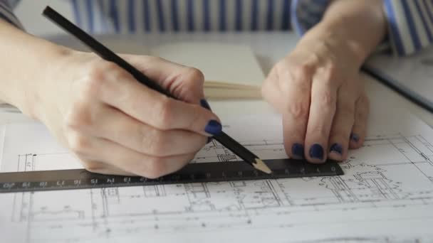 Zaměstnankyně čerpá plán s pravítko a tužka sedí v kanceláři