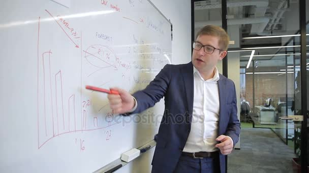 Man speaking in business suit and glasses points to graph on board.
