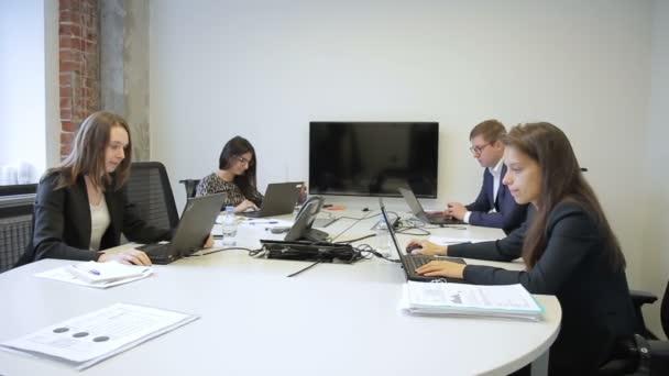 Mladí zaměstnanci práci s notebooky a mluví v moderní kanceláři. Muž v brýlích a tři ženy