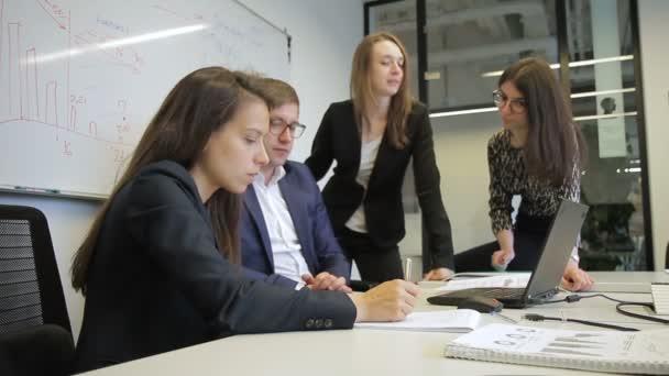 Des employés du groupe parlent tout en étant assis dans le bureau